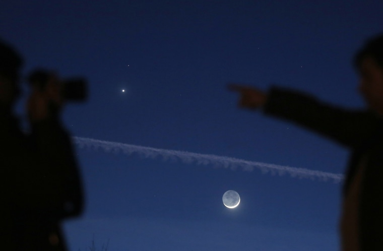 Image: A man takes pictures with the crescent moon and planets Venus and Mars visible in the sky in central Bosnia