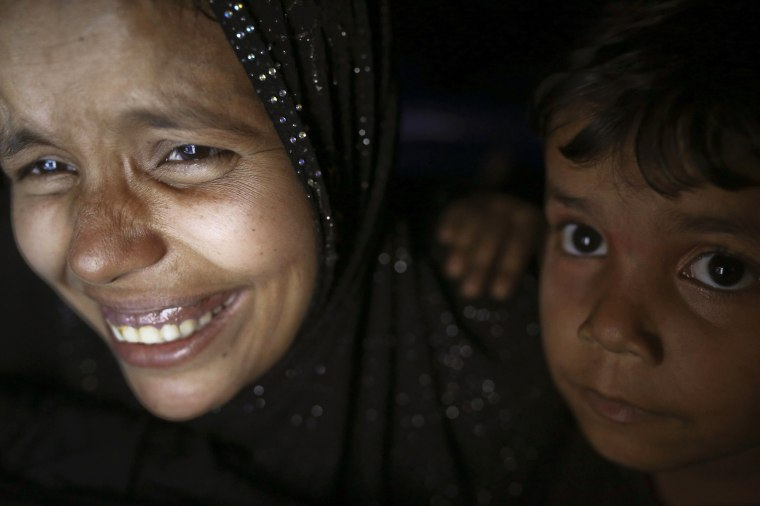 Image: Noor, a 28-year-old Rohingya woman, jokes with her husband at an internet hut in Thae Chaung village, near Sittwe