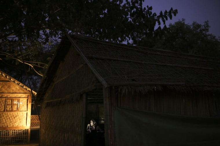Image: A woman speaks at a computer in an internet hut in Thae Chaung village, home to thousands of displaced Rohingya Muslims near Sittwe
