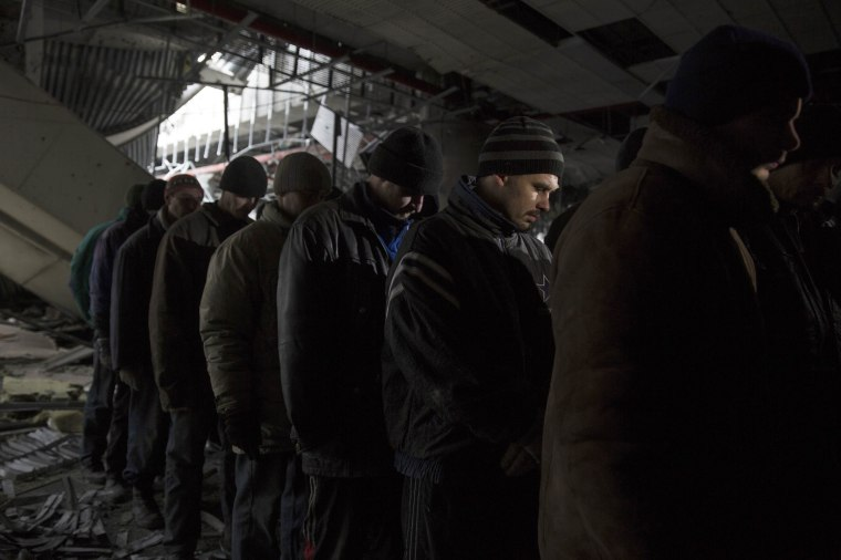 Image: Ukrainian war prisoners are guarded by armed men of the separatist self-proclaimed Donetsk People's Republic army in the Donetsk airport, damaged by months of fighting