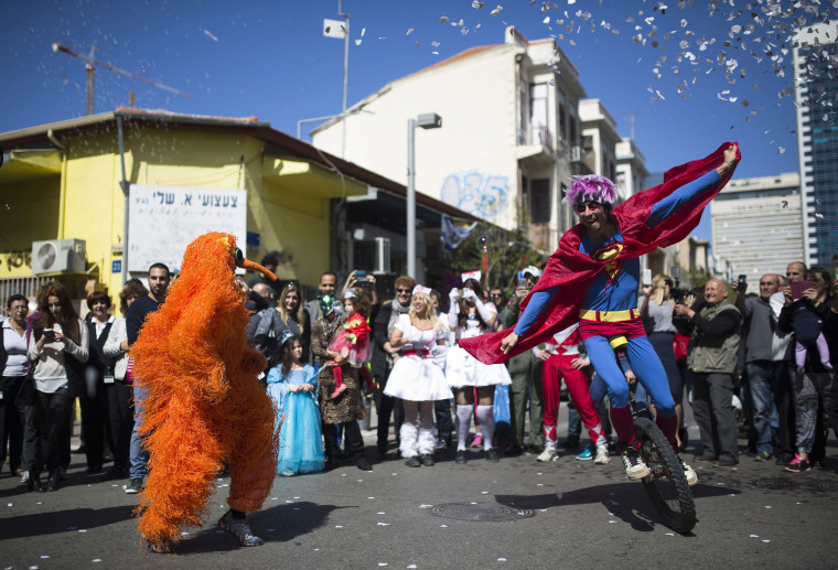 Image: Performers wearing costumes take part in a parade ahead of Purim in Tel Aviv