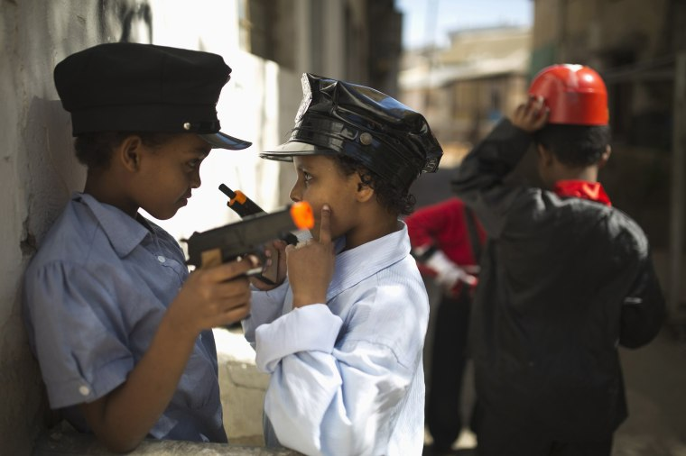 Image: Students wearing costumes play with toy guns during a parade for Purim in Tel Aviv