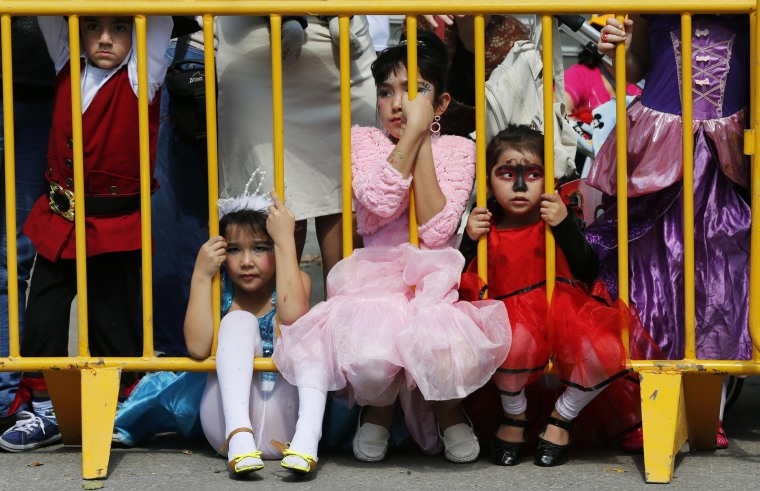 Image: Children dressed in costumes watch the annual parade marking the Jewish holiday of Purim in Holon