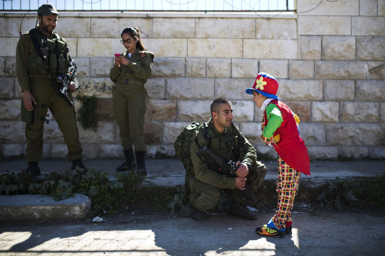 Image: A Jewish settler boy dressed in a costume speaks to an Israeli soldier during a parade marking Purim in Hebron