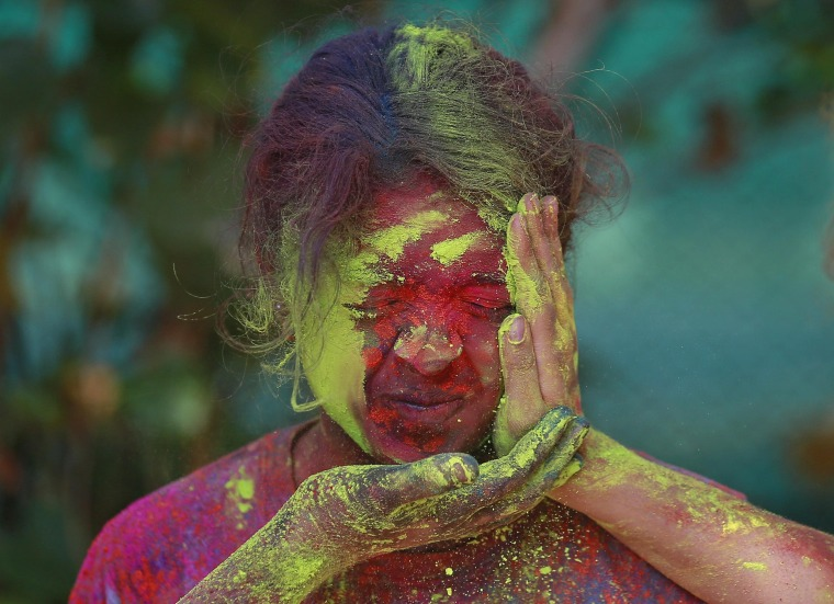 Image: Girl reacts as others apply coloured powder on her while celebrating Holi in Mumbai