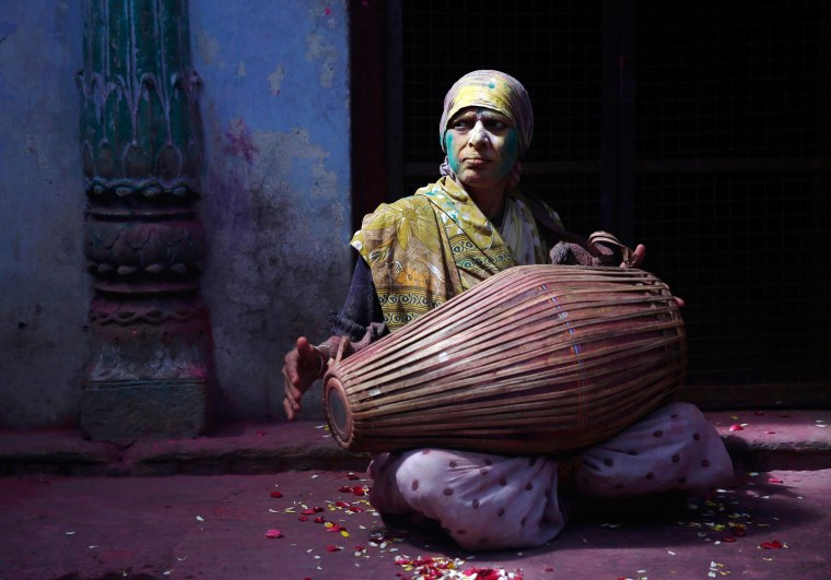 Image: A widow daubed in colours plays a drum during Holi celebrations organised by non-governmental organisation Sulabh International at widows' ashram at Vrindavan