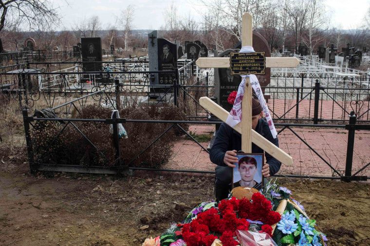 Image: A man places picture of worker Aleksandrov, killed by blast at Zasyadko coal mine, on grave during funeral ceremony in Donetsk