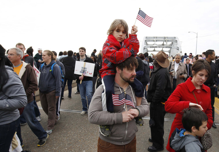 Image: Boy sits on his father's shoulders as they walk along the Edmund Pettus Bridge before the beginning of the 50th anniversary of the Selma to Montgomery civil rights march in Selma