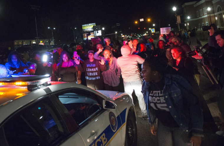 Image: Protestors block a police vehicle from entering the City of Ferguson Police Department and Municipal Court parking lot in Ferguson Missouri