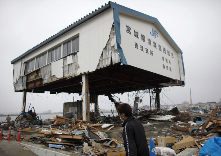 Image: A fisherman walks in a fishing port at an area that was devastated by the March 11 earthquake and tsunami, in Watari