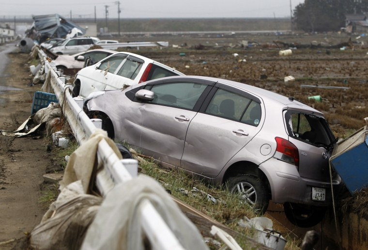 Image: Damaged cars are seen at an area that was devastated by the March 11 earthquake and tsunami, in Watari