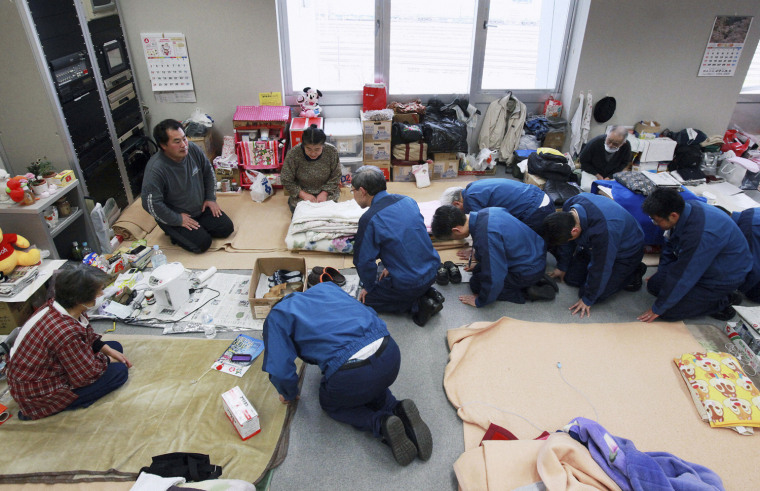 Image: TEPCO President Shimizu and company officials kneel as they bow to residents living in an evacuation centre in Koriyama