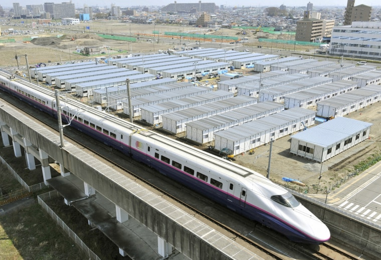 Image: The Shinkansen, or bullet train, is seen speeding past temporary houses for survivors of the earthquake and tsunami, in this photo taken by Kyodo in Sendai