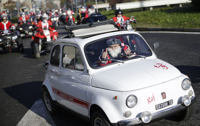 Image: A man dressed as Santa Claus drives his Fiat 500 during a charity event to support children at Regina Margherita hospital in Turin