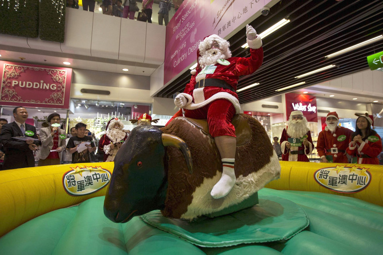 Image: A participant takes part in a competition, to determine who will represent Hong Kong at the annual Santa Claus Winter Games, at a shopping mall in Hong Kong