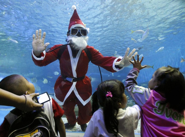 Image: A professional diver dressed as Santa Claus interacts with children as part of Christmas celebrations in Manila