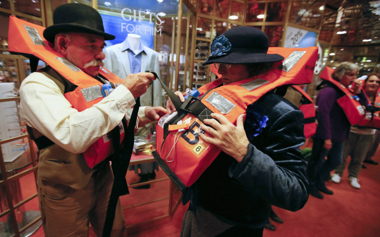Image: Australian cruise participants adjust their life jackets during a drill on board the Titanic Memorial Cruise in Southampton