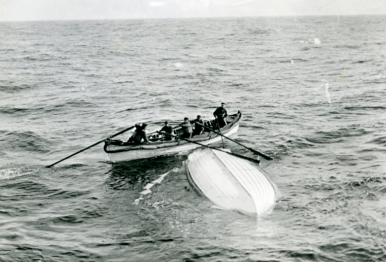 Image: A boat from the ship MacKay-Bennett examines an overturned lifeboat from the Titanic in waters of the Atlantic in 1912