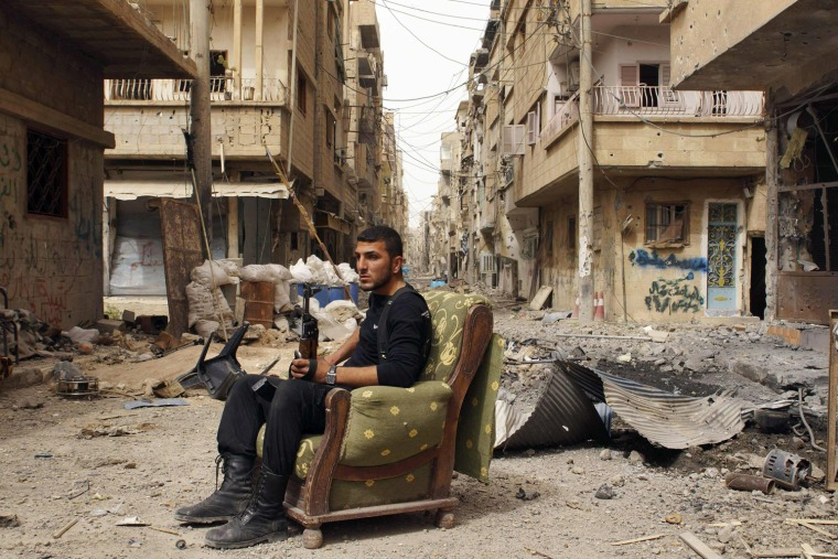 Image: Member of the Free Syrian Army holds his weapon as he sits on a sofa in the middle of a street in Deir al-Zor
