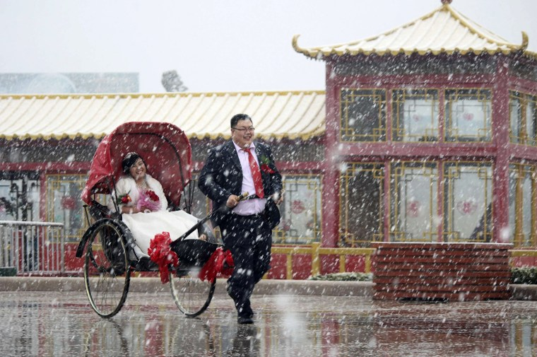 Image: A man pulls a rickshaw carrying his wife in a wedding gown during their wedding ceremony amid snowfall in Weihai