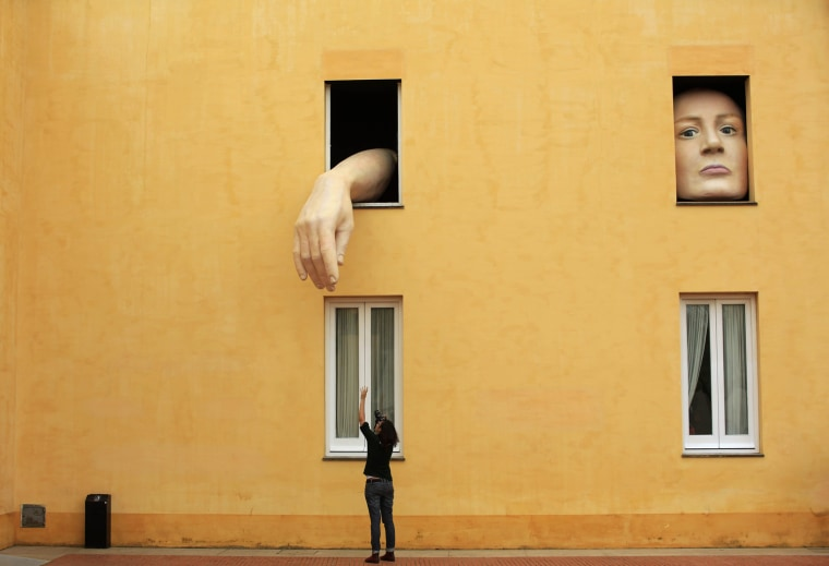 """Image: A woman takes pictures of art installation """"Alice"""" by Spanish artist Cristina Lucas in the Andalusian Centre of Contemporary Art in Seville"""