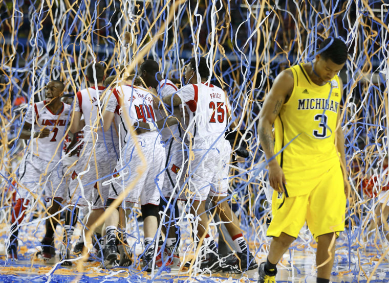 Image: Michigan Burke walks off the court as Louisville celebrates defeating Michigan to win the NCAA men's Final Four championship basketball game in Atlanta