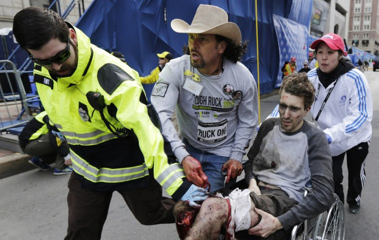 Image: Medical responders run an injured man past the finish line the 2013 Boston Marathon following an explosion in Boston