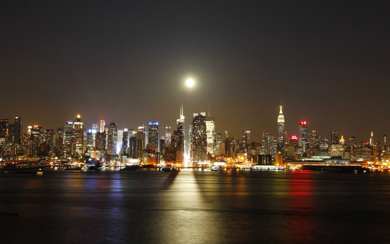 Image: A full moon rises over New York City above 42nd Street, as seen across the Hudson River in Weehawken, New Jersey