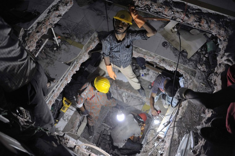 Image: Rescue workers attempt to rescue garment workers from the rubble of the collapsed Rana Plaza building, in Savar, 30 km (19 miles) outside Dhaka