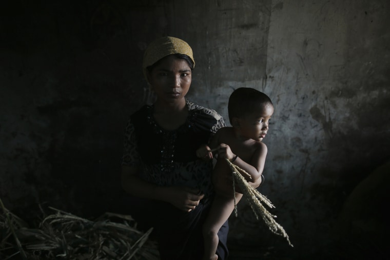 Image: Hla Hla May, Rohingya Muslim woman displaced by violence, holds her one year old daughter Roshan at former rubber factory near Sittwe