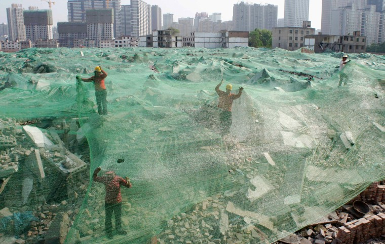 Image: Workers set up dust screen on a demolition site in Xi'an