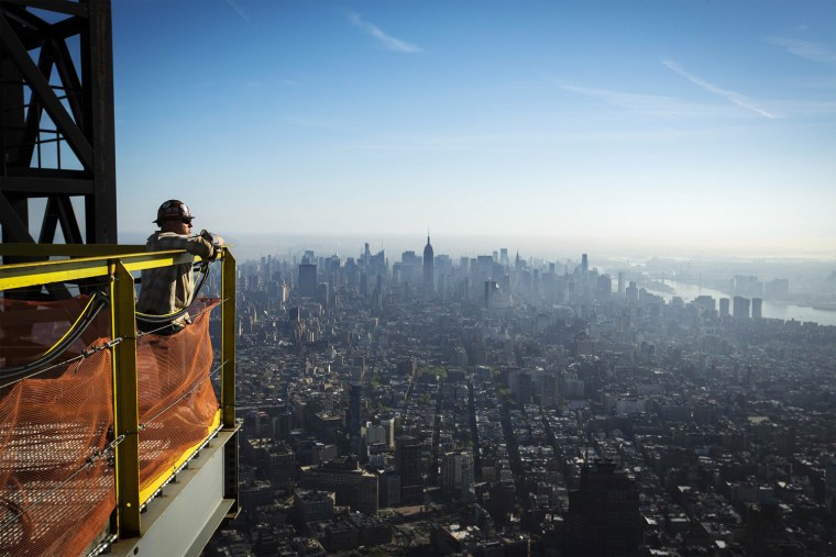 Image: An iron worker looks at the New York skyline after watching a crane lift the final piece of the spire to the top of the One World Trade Center in New York