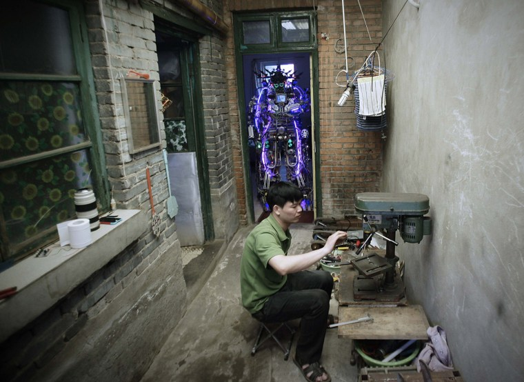 Image: Chinese inventor Tao Xiangli welds a component of his self-made robot at the yard of his house in Beijing