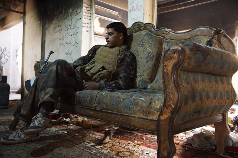 Image: A Free Syrian Army fighter sits on a sofa inside a house in Deir al-Zor