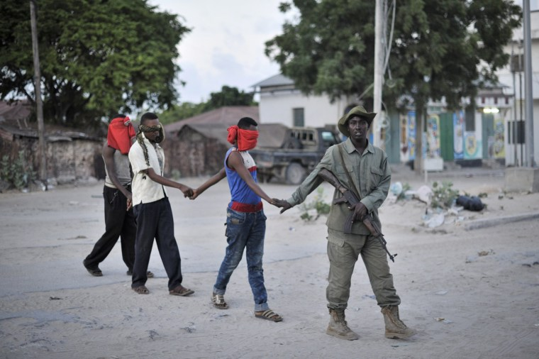 Image: A member of the Somali Police Force leads a group of blindfolded men to a holding area during an operation aimed at improving the security situation in Mogadishu