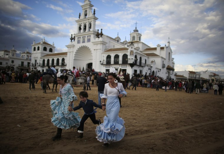 Image: Pilgrims run next to the shrine of El Rocio in Almonte, southern Spain
