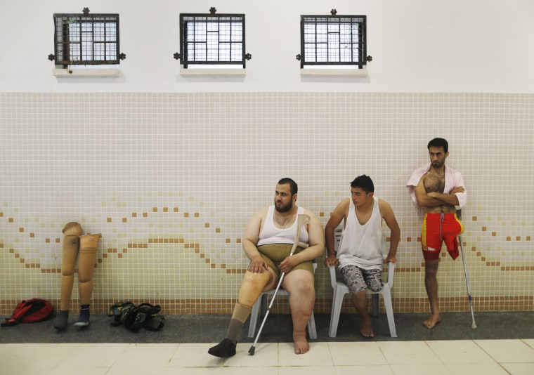 Image: Palestinians al-Masri, Abu Karsh, and Redwan rest after taking part in a swimming lesson inside al-Sadaka Club in Gaza City