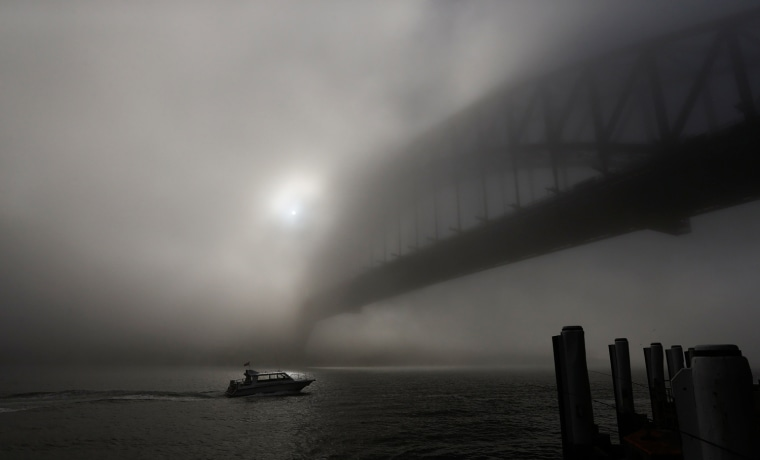 Image: A boat navigates past the Sydney Harbour Bridge, which is covered in thick fog