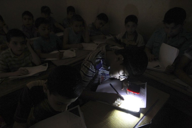 Image: A student wears a headlight, due to electricity shortage, as he takes his year-end examinations at a school in Aleppo's al-Sha'ar district