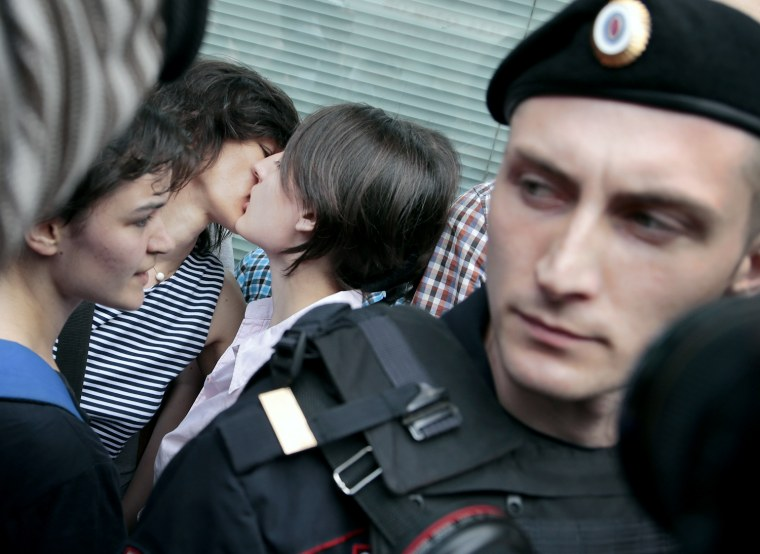 Image: Police officers watch gay rights activists kiss.