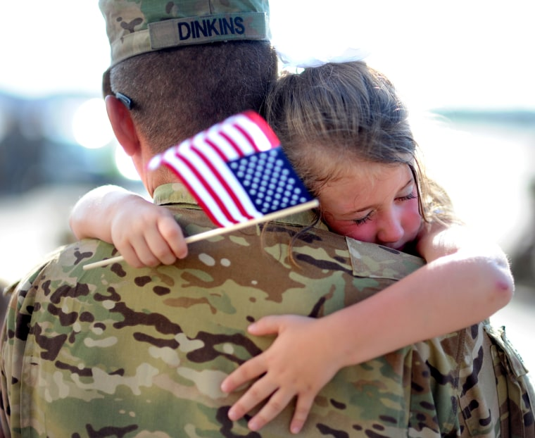 Image: U.S. Army Staff Sgt. Jason Dinkins with the 3rd Combat Aviation Brigade is hugged by his daughter.