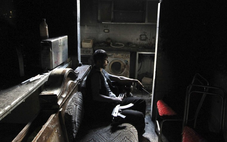 Image: A member of the Free Syrian Army sits with his weapon inside a house in Aleppo's al-Sayyid Ali neighborhood