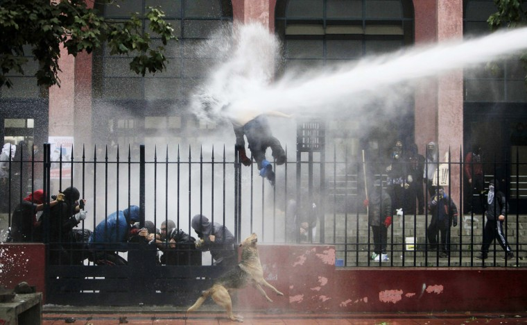 Image: A student is hit by a jet of water sprayed by riot police during a protest against the government to demand changes in the public state education system, in Santiago