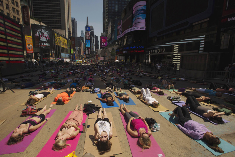 Image: People take part in a group yoga practice on the morning of the summer solstice in New York's Times Square