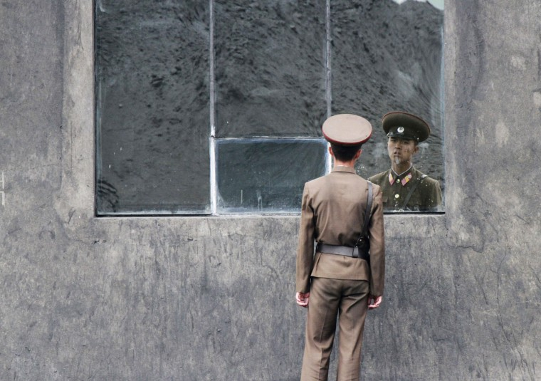 Image: A North Korea soldier stands in front of a window along the banks of Yalu River near the North Korean town of Sinuiju, opposite the Chinese border city of Dandong