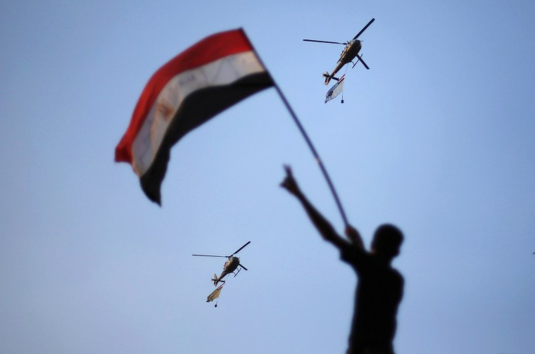 Image: Egyptian military helicopters trailing national flags circled over Tahrir Square during a protest demanding that Egyptian President Mohamed Mursi resign in Cairo