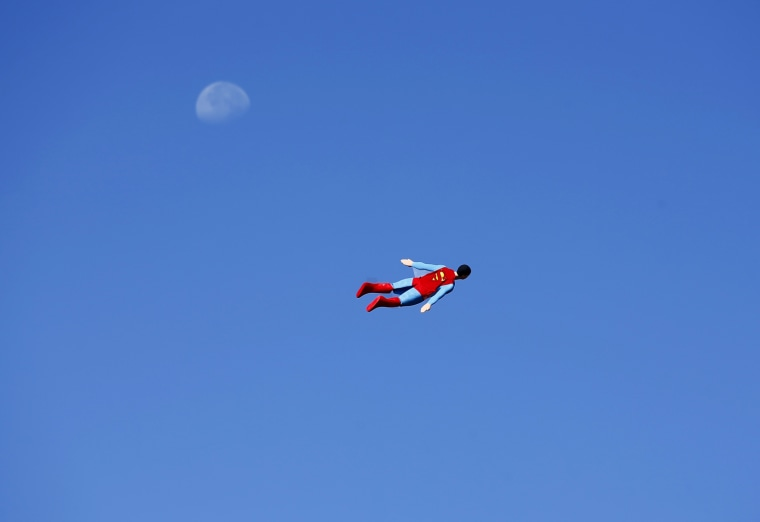 Image: A radio-controlled Superman plane, flown by designer Otto Dieffenbach, passes the moon during a test flight in San Diego