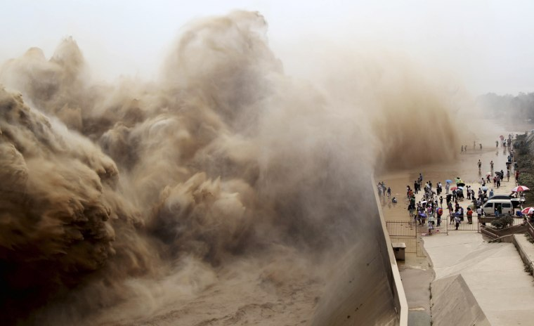 Image: Visitors watch water gushing from the section of the Xiaolangdi Reservoir on the Yellow River, during a sand-washing operation in Jiyuan