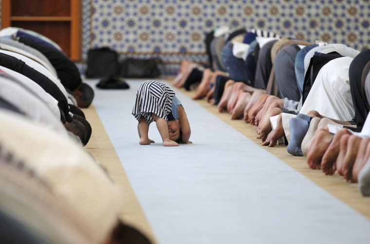 Image: A child is seen near members of the Muslim community attending midday prayers at Strasbourg Grand Mosque in Strasbourg