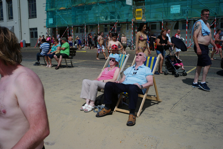 Image: A couple sunbathe near Bournemouth beach, in Bournemouth, southern England
